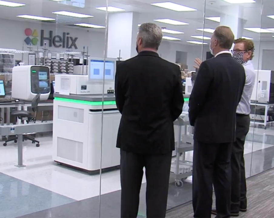 Testing takes place in the Helix laboratory, imaged here with Helix CEO Marc Stapley, the San Diego Mayor, and the Helix lab director looking in.