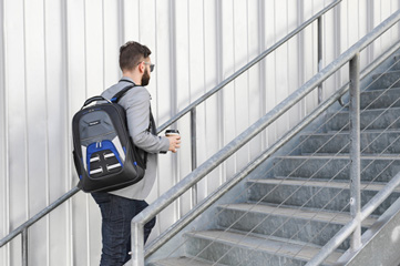 A man holding a coffee cup, wearing a Targus backpack, and walking up a set of stairs