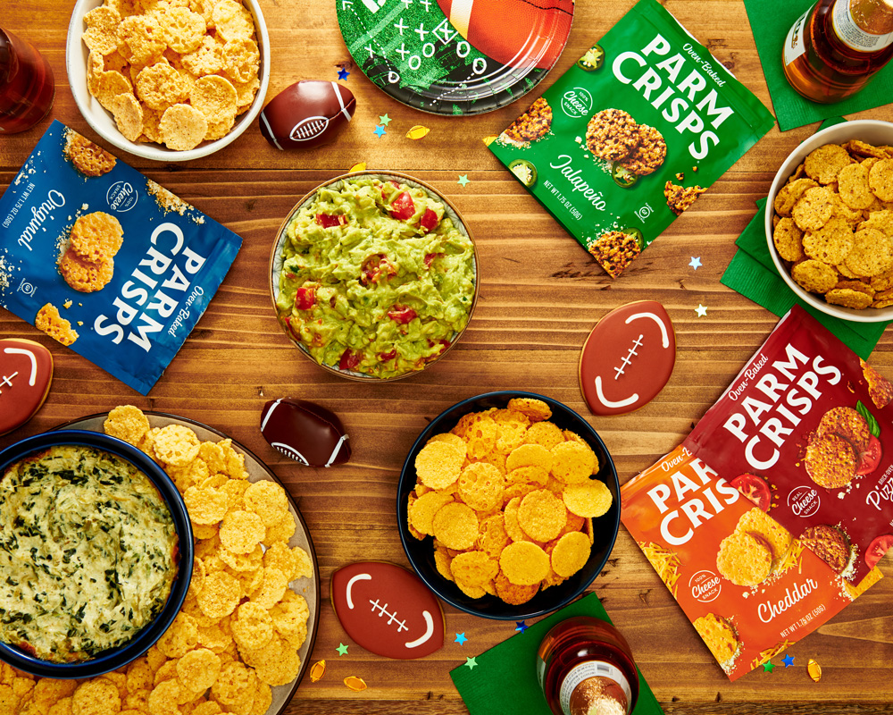 overhead shot of different ParmCrisps bags with bowls of guacamole and chips